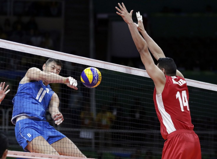 Italy's Simone Buti (11) spikes as Mexico's Tomas Aguilera (14) defends during a men's preliminary volleyball match at the 2016 Summer Olympics in Rio de Janeiro, Brazil, Thursday, Aug. 11, 2016. (AP Photo/Jeff Roberson)