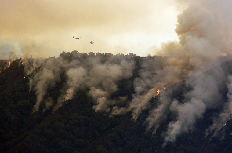 In this photo taken Tuesday, Aug. 2, 2016, helicopters work the Soberanes Fire west of Cachagua, Calif. A wildfire north of Big Sur near California's Central Coast has grown again overnight after burning for nearly two weeks. The fire has scorched more than 79 square miles and is less than 30 percent contained. It has destroyed 57 homes and is threatening another 2,000 structures. (Vern Fisher/Monterey Herald via AP)