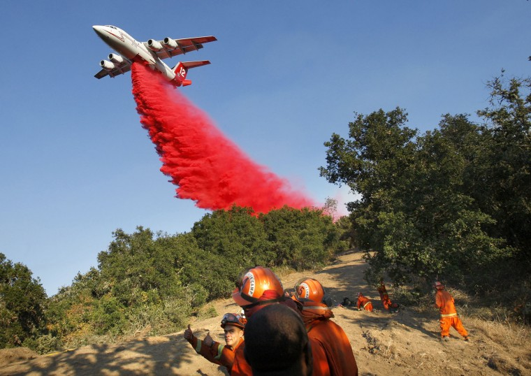 In this photo taken Tuesday, Aug. 2, 2016, an air tanker makes a drop of retardant over an inmate fire crew prior to a firing operation west of Cachagua, Calif. A wildfire north of Big Sur near California's Central Coast has grown again overnight after burning for nearly two weeks. The fire has scorched more than 79 square miles and is less than 30 percent contained. It has destroyed 57 homes and is threatening another 2,000 structures. (Vern Fisher/Monterey Herald via AP)