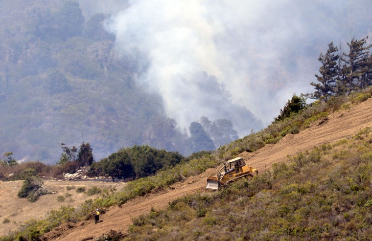 A dozer crew cut a containment line on Daniel's Ridge east of the Old Coast Road as firefighters battle the a wildfire in Big Sur, Calif., on Thursday, Aug. 4, 2016. A stubborn wildfire north of Big Sur near California's Central Coast has grown after burning for nearly two weeks in steep, forested ridges. (David Royal/The Monterey County Herald via AP)