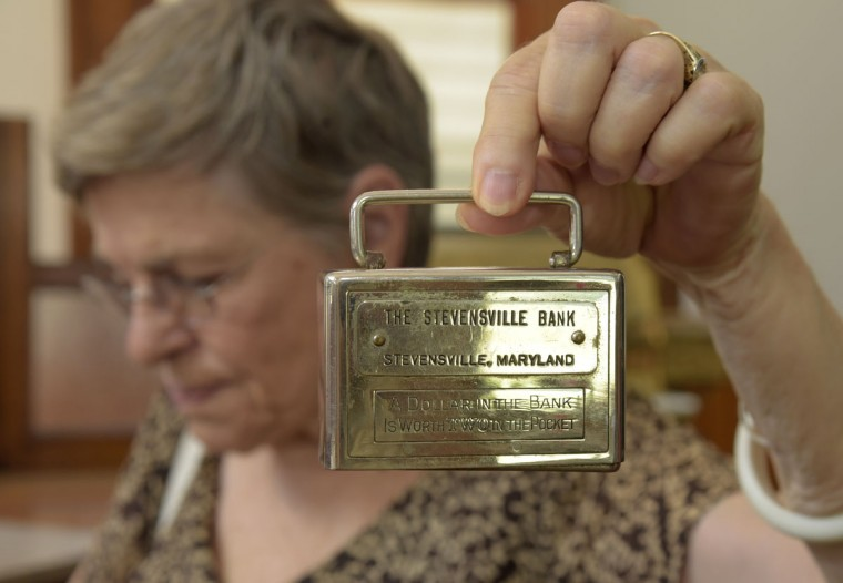 Nancy Cook, a docent with The Kent Island Heritage Society, Inc., holds up a small children's bank from The Historic Stevensville Bank of Queen Anne's County. (Algerina Perna/Baltimore Sun)