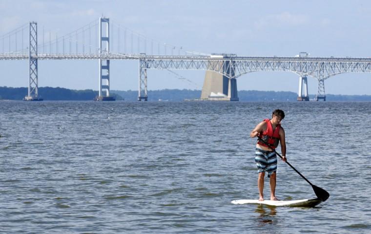 Jason Dinh, 38, paddle boards off Matapeake beach with the Bay Bridge as a backdrop. (Algerina Perna/Baltimore Sun)