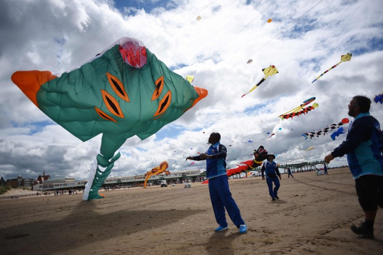 Members of the Kuwaiti Al Farsi Kite Team send up a kite as they participate in the St Annes Kite Festival on the seafront in Lytham St Annes, north west England on July 30, 2016. (OLI SCARFF/AFP/Getty Images)