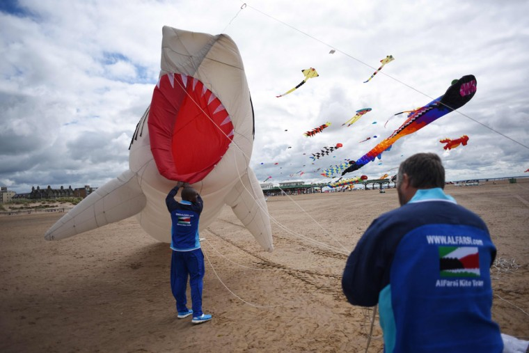 Members of the Kuwaiti Al Farsi Kite Team send up a shark kite as they participate in the St Annes Kite Festival on the seafront in Lytham St Annes, north west England on July 30, 2016. (OLI SCARFF/AFP/Getty Images)