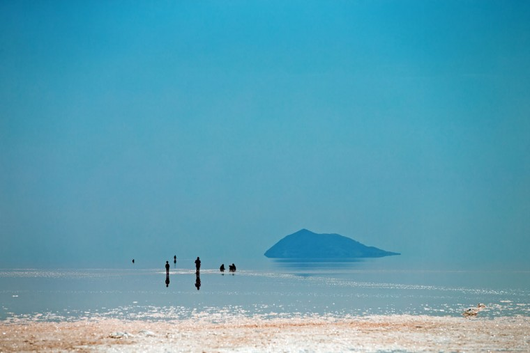 This picture taken on Friday, Aug. 26, 2016, shows Iranians spending time in Urmia Lake near Urmia, northwestern Iran. Hopes for survival of Urmia salt lake have been revived after more rains boosted a government program aimed at preserving the almost dried up water body. (AP Photo/Ebrahim Noroozi)