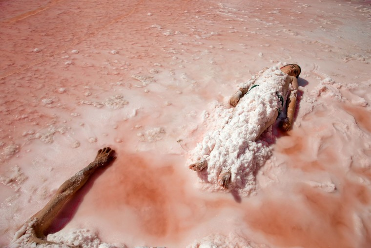 This picture taken on Friday, Aug. 26, 2016, shows Iranians lying beside Urmia Lake with their bodies covered with salt near Urmia, North-western Iran. Hopes for survival of Urmia salt lake have been revived after more rains boosted a government program aimed at preserving the almost dried up water body. (AP Photo/Ebrahim Noroozi)