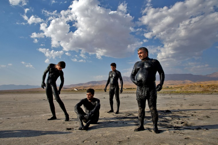 This picture taken on Saturday, Aug. 27, 2016, shows Iranians spend time beside Urmia Lake with their bodies covered with mud near Urmia, north-western Iran. Hopes for survival of Urmia salt lake have been revived after more rains boosted a government program aimed at preserving the almost dried up water body. (AP Photo/Ebrahim Noroozi)