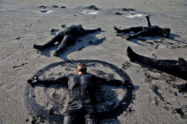 This picture taken on Saturday, Aug. 27, 2016, shows Iranians lying beside Urmia Lake with their bodies covered with mud near Urmia, northwestern Iran. Hopes for survival of Urmia salt lake have been revived after more rains boosted a government program aimed at preserving the almost dried up water body. (AP Photo/Ebrahim Noroozi)