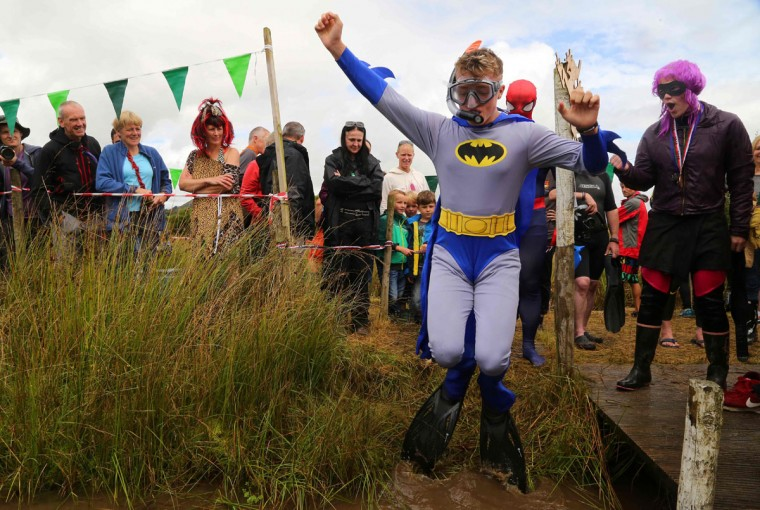 A man dressed as Batman jumps into the water as he takes part in the World Bog Snorkelling Championships in Waen Rhydd peat bog at Llanwrtyd Wells, south Wales on August 28, 2016. Entrants must negotiate two lengths of a 60-yard trench through the peat bog in the quickest possible time without using any conventional swimming strokes. (GEOFF CADDICK/AFP/Getty Images)