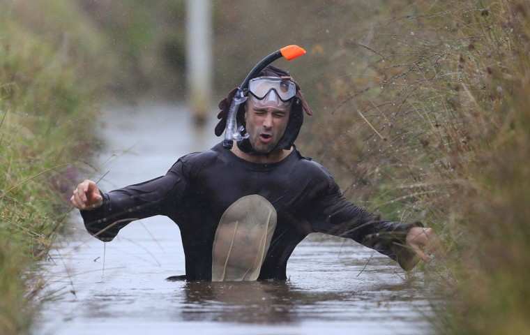 A competitor dressed as a reindeer takes part in the World Bog Snorkelling Championships in Waen Rhydd peat bog at Llanwrtyd Wells, south Wales on August 28, 2016. Entrants must negotiate two lengths of a 60-yard trench through the peat bog in the quickest possible time without using any conventional swimming strokes. (GEOFF CADDICK/AFP/Getty Images)