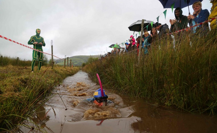 A competitor takes part in the World Bog Snorkelling Championships in Waen Rhydd peat bog at Llanwrtyd Wells, south Wales on August 28, 2016. Entrants must negotiate two lengths of a 60-yard trench through the peat bog in the quickest possible time without using any conventional swimming strokes. (GEOFF CADDICK/AFP/Getty Images)