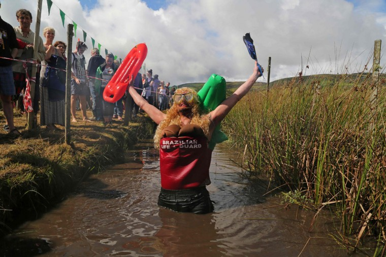 A man dressed as a lifeguard with a crocodile strapped to his back celebrates after he swims the course during the World Bog Snorkelling Championships in Waen Rhydd peat bog at Llanwrtyd Wells, south Wales on August 28, 2016. Entrants must negotiate two lengths of a 60-yard trench through the peat bog in the quickest possible time without using any conventional swimming strokes. (GEOFF CADDICK/AFP/Getty Images)