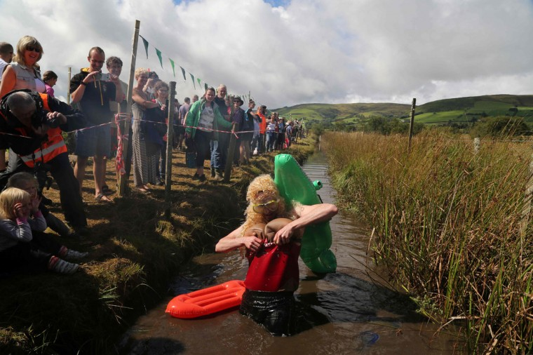 A man dressed as a lifeguard with a crocodile strapped to his back adjusts his costume after he swims the course during the World Bog Snorkelling Championships in Waen Rhydd peat bog at Llanwrtyd Wells, south Wales on August 28, 2016. Entrants must negotiate two lengths of a 60-yard trench through the peat bog in the quickest possible time without using any conventional swimming strokes. (GEOFF CADDICK/AFP/Getty Images)