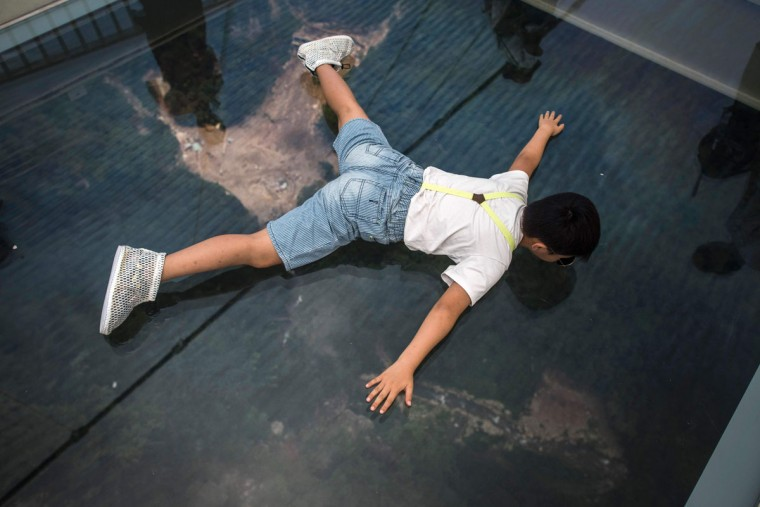 A boy lies down to see the view through the glass on the world's highest and longest glass-bottomed bridge above a valley in Zhangjiajie in China's Hunan Province on August 21, 2016. (FRED DUFOUR/AFP/Getty Images)