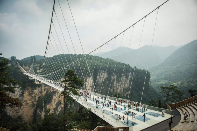 Visitors cross the world's highest and longest glass-bottomed bridge above a valley in Zhangjiajie in China's Hunan Province on August 21, 2016. (FRED DUFOUR/AFP/Getty Images)