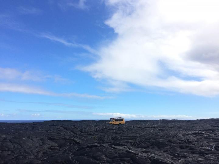 In this Monday, Aug. 8, 2016 photo, a school bus being used as a homestead sits on private property atop a former lava flow from Kilauea, an active volcano on Hawaii's Big Island, near Volcanoes National Park in Kalapana, Hawaii. People who lost their homes to previous lava flows have begun rebuilding on top of the hardened lava rock. The current lava flow a few miles away erupted from a vent on the volcano in May and made its way to the sea in late July. Visitors can hike about 10 miles round trip to see the lava, or take a boat or helicopter tour to see the flow. (AP Photo/Caleb Jones)