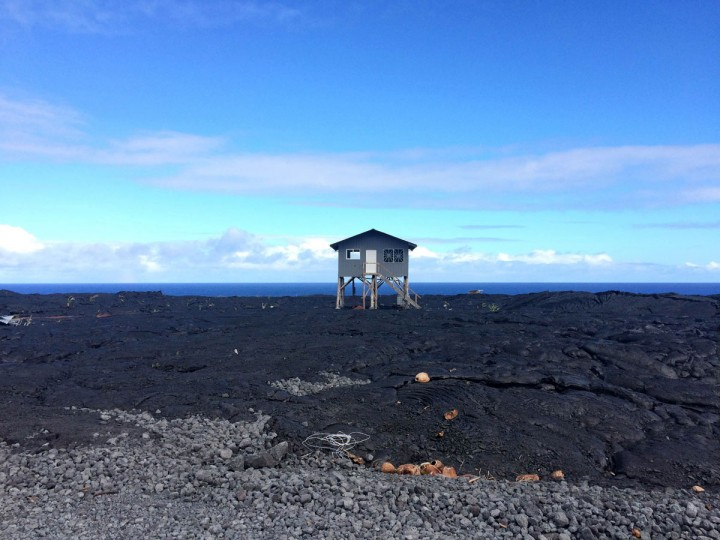 In this Monday, Aug. 8, 2016 photo, a small home sits on private property atop a former lava flow from Kilauea, an active volcano on Hawaii's Big Island, near Volcanoes National Park in Kalapana, Hawaii. People who lost their homes to previous lava flows have begun rebuilding on top of the hardened lava rock. The current lava flow a few miles away erupted from a vent on the volcano in May and made its way to the sea in late July. Visitors can hike about 10 miles round trip to see the lava, or take a boat or helicopter tour to see the flow. (AP Photo/Caleb Jones)