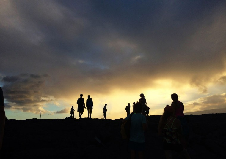 In this Monday, Aug. 8, 2016 photo, visitors hike onto a lava flow from Kilauea, an active volcano on Hawaii's Big Island, in Volcanoes National Park near Kalapana, Hawaii. The current lava flow erupted from a vent on the volcano in May and made its way to the sea in late July. Visitors can hike about 10 miles round trip to see the lava, or take a boat or helicopter tour to see the flow. (AP Photo/Caleb Jones)