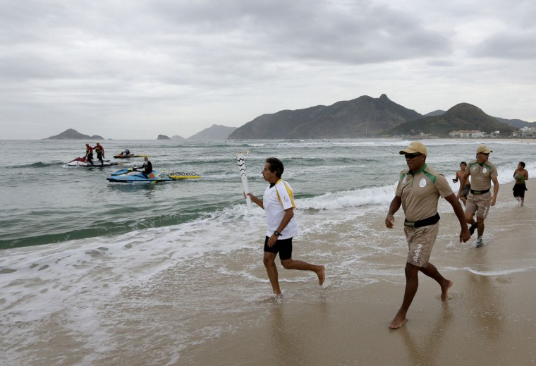 Brazilian Rico de Souza runs on the beach as he prepares to surf with the Olympic torch at Macumba beach as the torch relay continues on its journey to the opening ceremony of Rio's 2016 Summer Olympics, in Rio de Janeiro, Brazil, Thursday, Aug. 4, 2016. (AP Photo/Charlie Riedel)