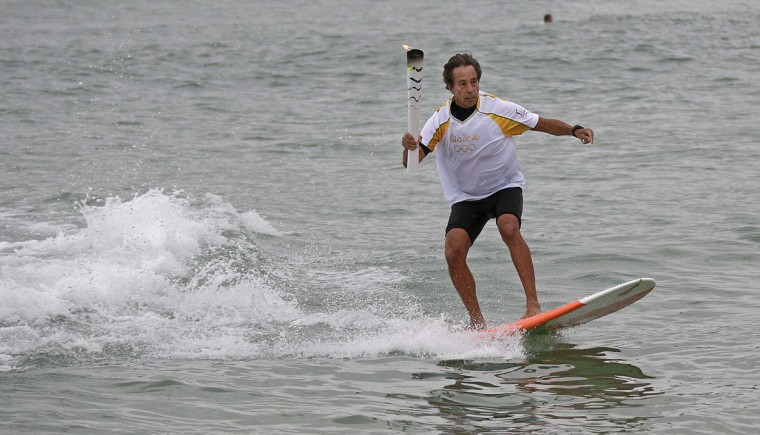 Brazilian Rico de Souza surfs with the Olympic torch at Macumba beach at Recreio dos Bandeirantes as torch relay continues on its journey to the opening ceremony of Rio's 2016 Summer Olympics, in Rio de Janeiro, Brazil, Thursday, Aug. 4, 2016. (AP Photo/Charlie Riedel)