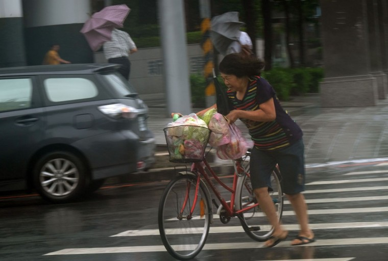 A woman pushes her bicycle during a storm in Panchiao district, New Taipei City, as Typhoon Megi hit eastern Taiwan on September 27, 2016. Taiwan went into shutdown on September 27 as the island faces its third typhoon in two weeks, with thousands evacuated, schools and offices closed across the island and hundreds of flights disrupted. (SAM YEH/AFP/Getty Images)
