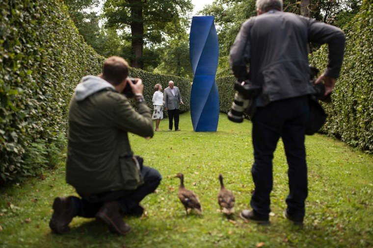 Members of the media, assisted by a pair of ducks, photograph Peregrine 'Stoker' Cavendish (center right), Duke of Devonshire, and his wife Amanda, Duchess of Devonshire in front of a sculpture by artist Alexander MacDonald-Buchanan entitled 'Energy 2' that features in the 'Beyond Limits' exhibition in the grounds of Chatsworth House near Bakewell, northern England, on September 9, 2016. (OLI SCARFF/AFP/Getty Images)