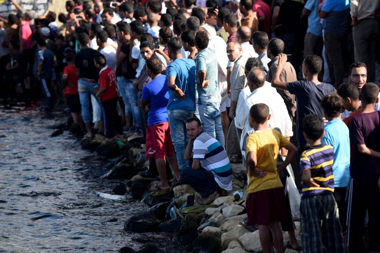Egyptians stand on the shore as they wait for the recovery of bodies, during a search operation after a boat carrying migrants capsized in the Mediterranean, along the shore in the Egyptian port city of Rosetta on September 21, 2016. A boat carrying up to 450 migrants capsized in the Mediterranean off Egypt's north coast, drowning 42 people and prompting a search operation that rescued 163 passengers, officials said. (Mohamed El-Shahed/AFP/Getty Images)