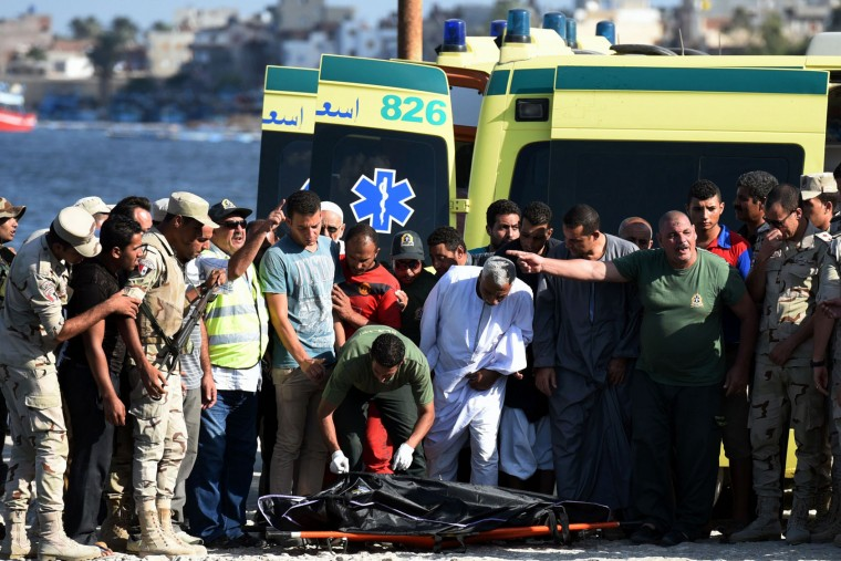 Egyptian medics cover the body of a migrant along the shore in the Egyptian port city of Rosetta on September 21, 2016, during a search operation after a boat carrying migrants capsized in the Mediterranean. A boat carrying up to 450 migrants capsized in the Mediterranean off Egypt's north coast, drowning 42 people and prompting a search operation that rescued 163 passengers, officials said. (Mohamed El-Shahed/AFP/Getty Images)