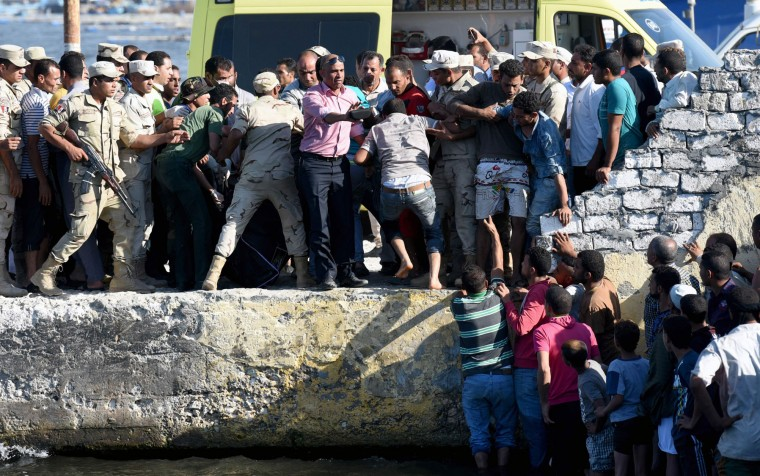 Egyptian men and policemen react upon the arrival of the bodies of migrants along the shore in the Egyptian port city of Rosetta on September 21, 2016, during a search operation after a boat carrying migrants capsized in the Mediterranean. A boat carrying up to 450 migrants capsized in the Mediterranean off Egypt's north coast, drowning 42 people and prompting a search operation that rescued 163 passengers, officials said. (Mohamed El-Shahed/AFP/Getty Images)