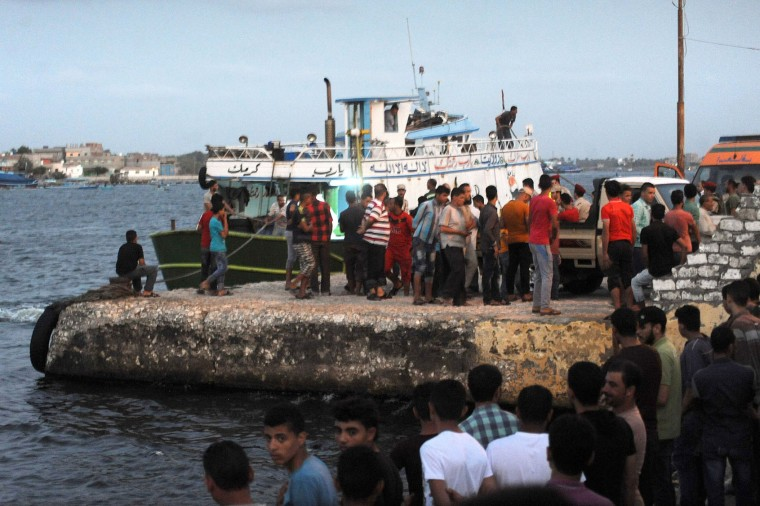 People gather along the shore in the Egyptian port city of Rosetta on September 21, 2016, during a search operation after a boat carrying migrants capsized in the Mediterranean. A boat carrying up to 450 migrants capsized in the Mediterranean off Egypt's north coast, drowning 42 people and prompting a search operation that rescued 163 passengers, officials said. (Stringer/AFP/Getty Images)