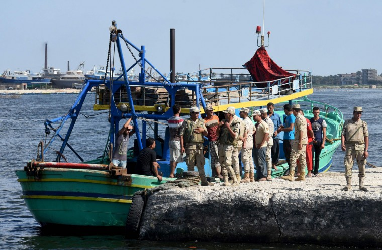 Egyptian men and policemen gather along the shore in the Egyptian port city of Rosetta on September 21, 2016, during a search operation after a boat carrying migrants capsized in the Mediterranean. A boat carrying up to 450 migrants capsized in the Mediterranean off Egypt's north coast, drowning 42 people and prompting a search operation that rescued 163 passengers, officials said. (Mohamed El-Shahed/AFP/Getty Images)