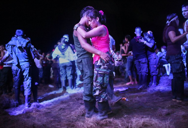 FARC rebels and supporters dance at a concert at the 10th Guerrilla Conference in the remote Yari plains where the peace accord was in the process of being ratified by the FARC on September 21, 2016 in El Diamante, Colombia. The peace agreement attempts to end the 52-year-old guerrilla war between the FARC and the state, the longest-running armed conflict in the Americas which left 220,000 dead. The final agreement is set to be signed on September 26 and will then be put to vote by the public in a referendum on October 2. The plan calls for a disarmament and re-integration of most of the estimated 7,000 FARC fighters. (Photo by Mario Tama/Getty Images)