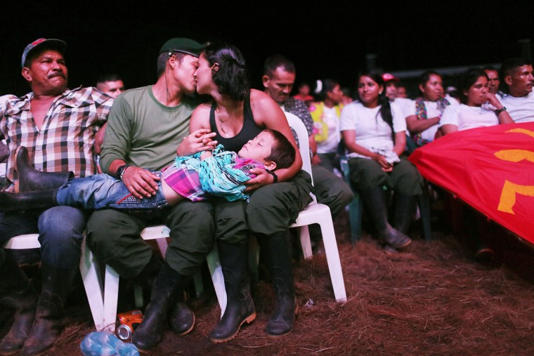 FARC guerrillas Willington (2nd L) and Veronica (noms de guerre) kiss while holding their nephew at the 10th Guerrilla Conference in the remote Yari plains where the peace accord was in the process of being ratified on September 22, 2016 in El Diamante, Colombia. The peace agreement attempts to end the 52-year-old guerrilla war between the FARC and the state, the longest-running armed conflict in the Americas which left 220,000 dead. The final agreement is set to be signed on September 26 and will then be put to vote by the public in a referendum on October 2. The plan calls for a disarmament and re-integration of most of the estimated 7,000 FARC fighters. (Photo by Mario Tama/Getty Images)