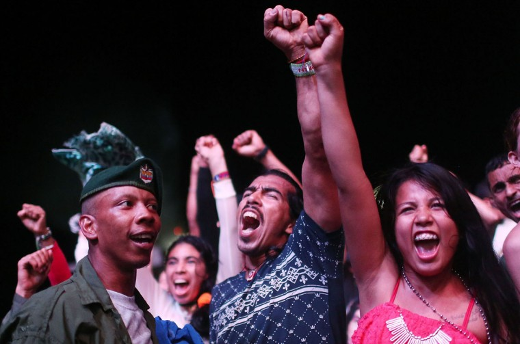 FARC guerrillas and supporters celebrate at a concert at the 10th Guerrilla Conference in the remote Yari plains where the peace accord was in the process of being ratified by the FARC on September 21, 2016 in El Diamante, Colombia. The peace agreement attempts to end the 52-year-old guerrilla war between the FARC and the state, the longest-running armed conflict in the Americas which left 220,000 dead. The final agreement is set to be signed on September 26 and will then be put to vote by the public in a referendum on October 2. The plan calls for a disarmament and re-integration of most of the estimated 7,000 FARC fighters. (Photo by Mario Tama/Getty Images)