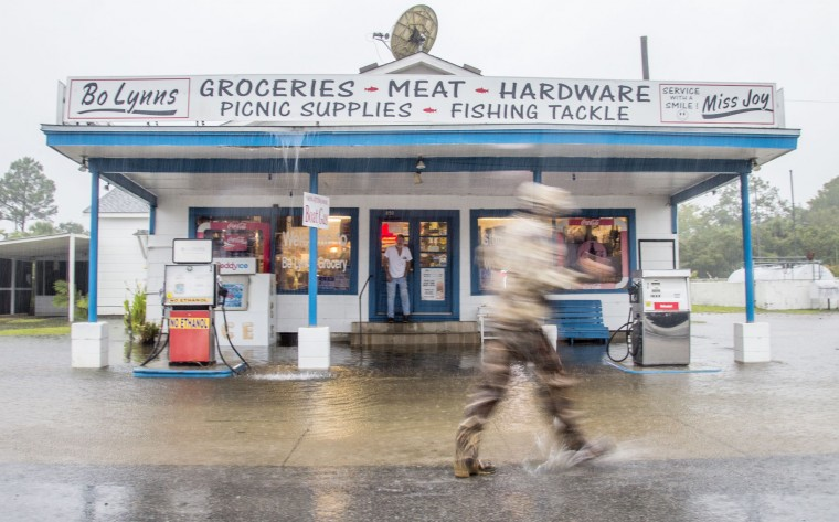 A person wades through the storm surge from Hurricane Hermine past Bo Lynns Grocery on September 1, 2016 in Saint Marks, Florida. Hurricane warnings have been issued for parts of Florida's Gulf Coast as Hermine is expected to make landfall as a Category 1 hurricane (Photo by Mark Wallheiser/Getty Images)