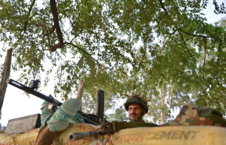 An Indian army soldier keeps vigil at an outpost near the India-Pakistan border in Abdullian, southwest of Jammu on September 30, 2016. India evacuated thousands of people living near the border with Pakistan on September 30, a day after carrying out strikes along the de-facto frontier in disputed Kashmir that have dramatically escalated tensions between the nuclear-armed neighbours. / (AFP Photo/Tauseef Mustafa)