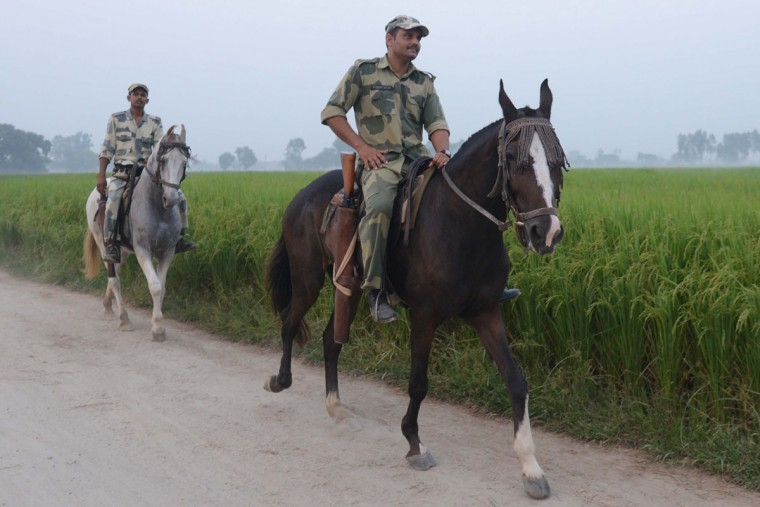 Indian Border Security Force (BSF) personnel patrol on horses at the India-Pakistan border village Daoke, about 40 kms from Amritsar on September 30, 2016. India evacuated thousands of people living near the border with Pakistan on September 30, a day after carrying out strikes along the de-facto frontier in disputed Kashmir that have dramatically escalated tensions between the nuclear-armed neighbours. / (AFP Photo/Narinder Nanu)