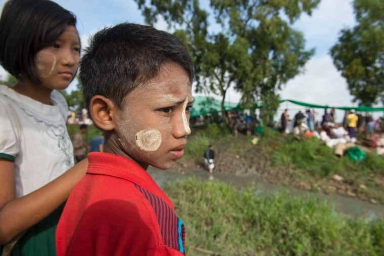 Children wearing traditional facial paste wait to get rations of meat during a religious sacrifice of animals by Myanmar's Muslim minority in a muddy field, seen in the background, in observance of Eid al-Adha on September 13, 2016 in Thanlyin township instead of the town center, a move they said was because of complaints from some Buddhist residents. Muslims across the world are celebrating the annual festival of Eid al-Adha, or the festival of sacrifice, which marks the end of the Hajj pilgrimage to Mecca and commemorates prophet Abraham's readiness to sacrifice his son to show obedience to God. (Romeo Gacad/AFP/Getty Images)