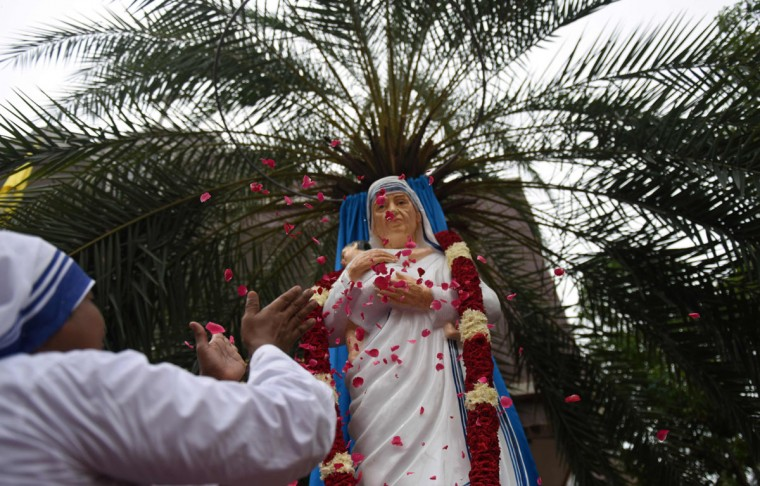 An Indian nun showers rose petals as she pays obeisance to a statue of Mother Teresa unveiled at a church in Chennai on September 4, 2016, ahead of the canonisation of Mother Teresa in Rome. Indian Christians are eagerly looking forward to the canonisation of Mother Teresa and churches across the country are holding special masses in her honour. As the Vatican prepares to declare Mother Teresa a saint on September 4, in the Indian city where she rose to fame, claims of medical negligence and financial mismanagement at her care homes threaten to cloud her legacy. (AFP PHOTO / ARUN SANKAR)