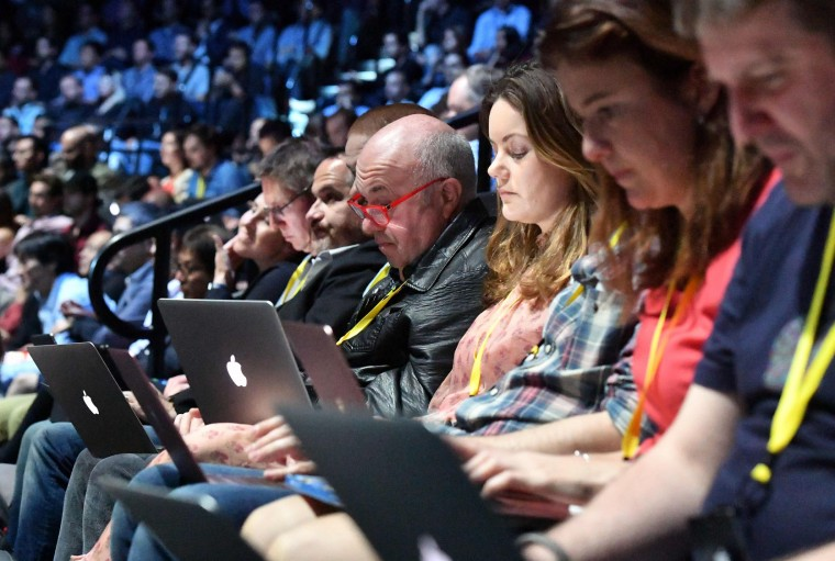 Audience members engage with their devices while Apple CEO Tim Cook speaks on stage during a media event at Bill Graham Civic Auditorium in San Francisco, California on September 07, 2016. (Josh Edelson/AFP/Getty Images)