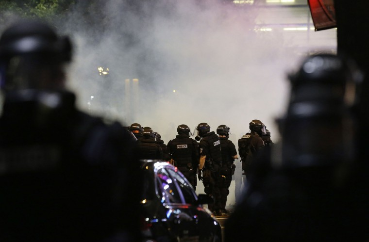 Police fire teargas as protestors converge on downtown following Tuesday's police shooting of Keith Lamont Scott in Charlotte, N.C., Wednesday, Sept. 21, 2016. Protesters have rushed police in riot gear at a downtown Charlotte hotel and officers have fired tear gas to disperse the crowd. At least one person was injured in the confrontation, though it wasn't immediately clear how. Firefighters rushed in to pull the man to a waiting ambulance. (AP Photo/Gerry Broome)