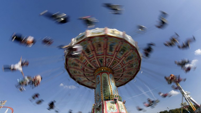 In this photo taken with a long time exposure people enjoy a swing ride at the 183rd Oktoberfest beer festival in Munich, Germany, Monday, Sept. 26, 2016. The world's largest beer festival will be held from Sept. 17 to Oct. 3, 2016. (AP Photo/Matthias Schrader)