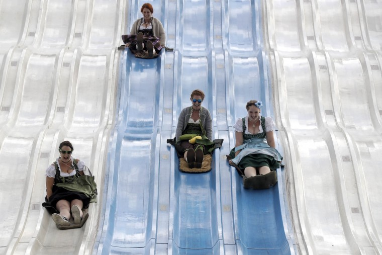 People enjoy a fun slide at the 183rd Oktoberfest beer festival in Munich, southern Germany, Tuesday, Sept. 20, 2016. The world's largest beer festival will be held from Sept. 17 to Oct. 3, 2016. (AP Photo/Matthias Schrader)