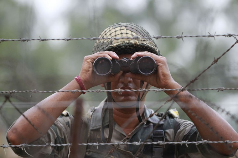 In this Sept. 24, 2016 file photo, an Indian Border Security Force soldier looks at the Pakistan side of the border through a binocular at Ranbir Singh Pura, about 35 kilometers (22 miles) from Jammu, India. In New Delhi, they say that highly trained Indian soldiers slipped across the de facto border and into Pakistani-controlled Kashmir in a daring nighttime raid, killing anti-India militants preparing to launch attacks. In Islamabad, they say that only one Indian soldier made it across the border, and he was captured, with Pakistani forces easily driving back the other Indians, who retreated as soon as they encountered resistance. The dueling tales of courageous forces serve politics on both sides of the border, with powerful forces in each country able to proclaim their courage in the face of aggression. (AP Photo/Channi Anand, File)