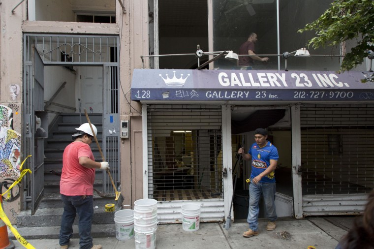 Workers clean up a storefront gallery on W. 23rd St. in Manhattan, Tuesday, Sept. 20, 2016, in New York. The gallery's windows were shattered by shrapnel from the bomb that exploded across the street Saturday evening. An Afghan immigrant wanted in the bombings was captured Monday after being wounded in a gun battle with police. (AP Photo/Mark Lennihan)