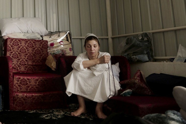 In this Sunday, Sept. 11, 2016 photo, an Iraqi woman uses her prayer beads to make tasbeeh, or meditation, inside the women's camp in Arafat during the annual hajj pilgrimage, near the holy city of Mecca, Saudi Arabia. (AP Photo/Nariman El-Mofty)