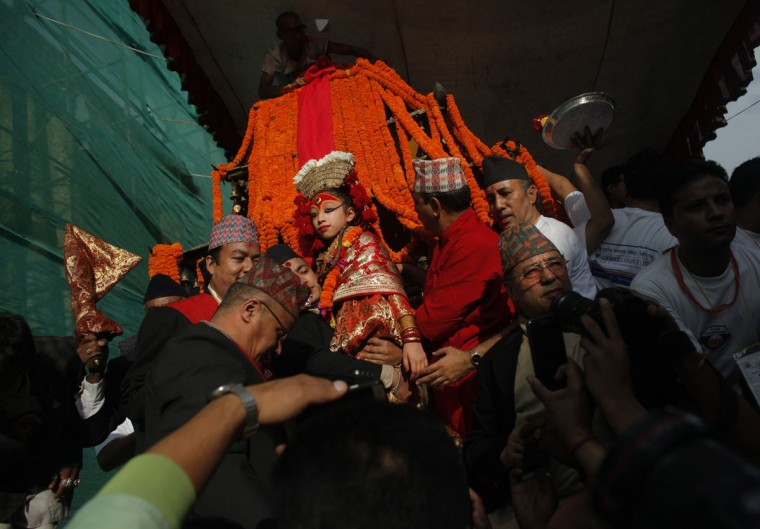 Nepal's living goddess, centre, is taken in a wooden chariot during the Indra Jatra festival in Kathmandu, Nepal, Thursday, Sept.15, 2016. Selected as toddlers, living goddesses known locally as Kumaris are worshipped and they usually keep their positions until they reach puberty. Indra is considered the Hindu god of rain and the festival marks the end of the rainy season. (AP Photo/Niranjan Shrestha)