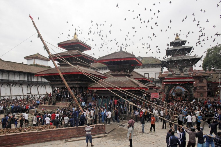 Nepalese devotees erect a wooden pole in front of the ancient royal palace on the beginning of the week-long Indra Jatra festival at Basantapur Durbar Square in Kathmandu, Nepal, Tuesday, Sept. 13, 2016. Indra is considered the Hindu god of rain and the festival marks the end of the rainy season. (AP Photo/Niranjan Shrestha)