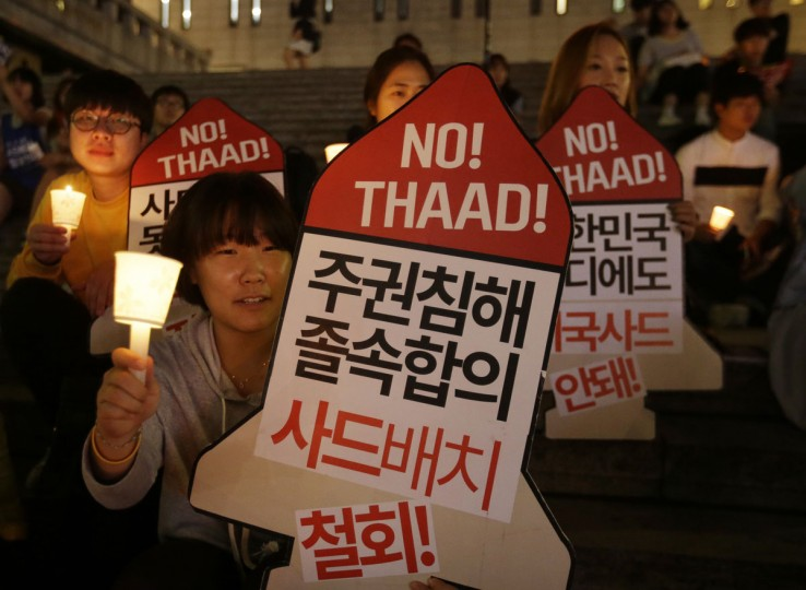 """South Korean protesters stage a rally to oppose a deployment of the Terminal High-Altitude Area Defense, or THAAD, in Seoul, South Korea, Friday, Sept. 9, 2016. North Korea said Friday it conducted a """"higher level"""" nuclear warhead test explosion that will allow it to finally build """"at will"""" an array of stronger, smaller and lighter nuclear weapons. It is Pyongyang's fifth atomic test and the second in eight months. The signs read """"We oppose the THAAD deployment."""" (AP Photo/Ahn Young-joon)"""