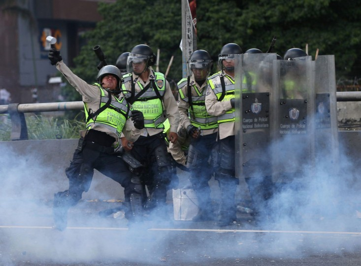 "In this Sept 1, 2016. photo, a Bolivarian police officer hurls a tear gas canister at demonstrators during a protest in Caracas, Venezuela. Venezuela's opposition is vowing to keep up pressure on President Nicolas Maduro after flooding the streets of Caracas with demonstrators Thursday in its biggest show of force in years. Protesters filled dozens of city blocks in what was dubbed the ""taking of Caracas"" to pressure electoral authorities to allow a recall referendum against Maduro this year.(AP Photo/Fernando Llano)"